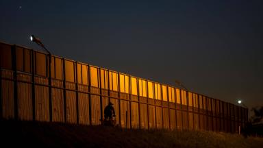 A border patrol agent drives along the US- Mexico border crossing.