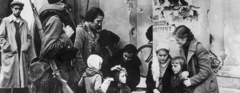 Polish women tend to their children while a soldier looks on during the German siege of Warsaw, Poland. (Getty)