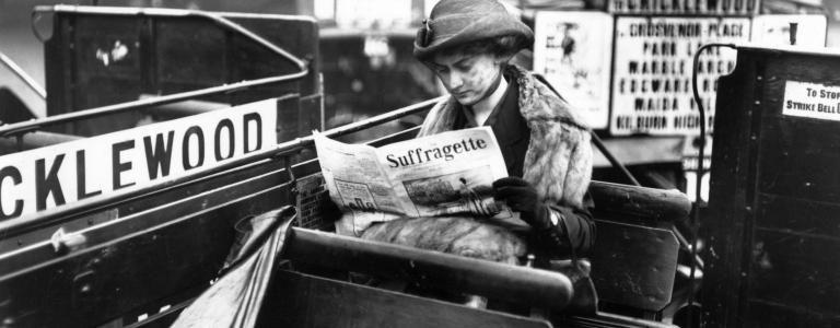 A woman reading a copy of the 'Suffragette' magazine on an open-top London bus.