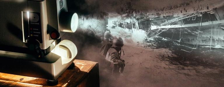 Photo of a projector and a World War Two image of a flugzeugträger bombing